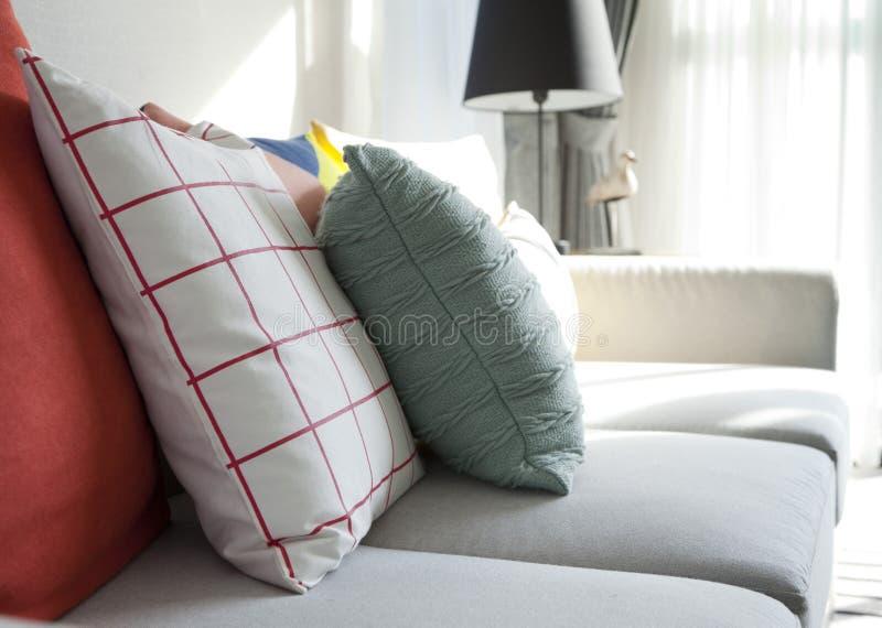 Descansos coloridos em um sofá cinzento imagens de stock
