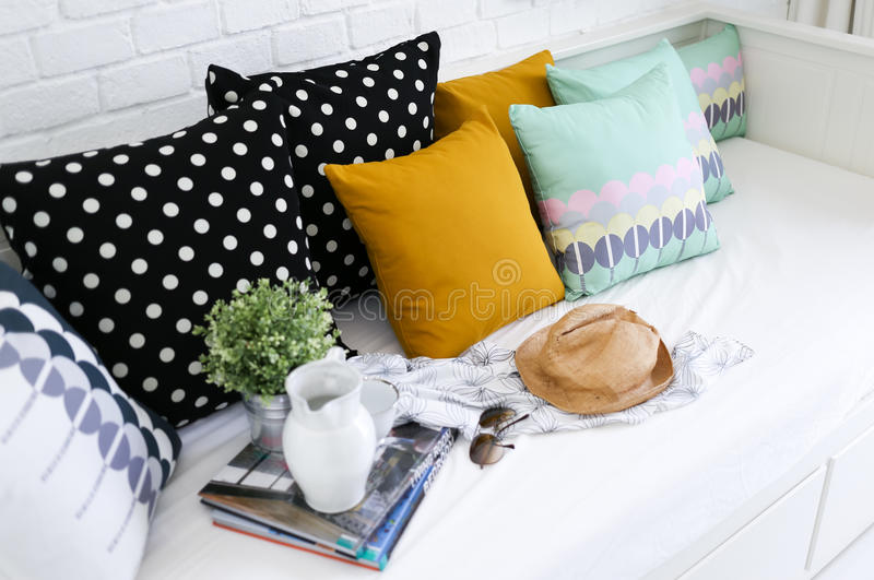 Descansos coloridos em um sofá com a parede de tijolo branca mim imagem de stock