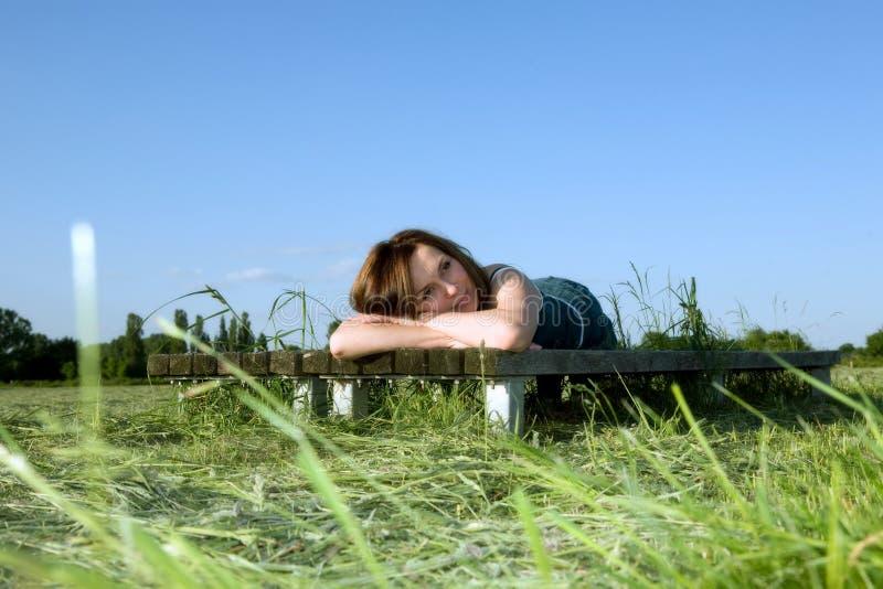 Descansos da mulher na grama verde imagens de stock