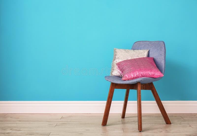 Descansos diferentes na cadeira perto da parede da cor foto de stock