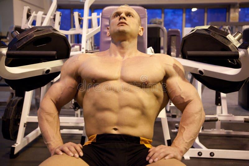 Descansos do Bodybuilder no quarto do treinamento fotos de stock royalty free