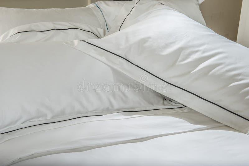 Descansos e cama branca no quarto branco Roupa de cama imagem de stock