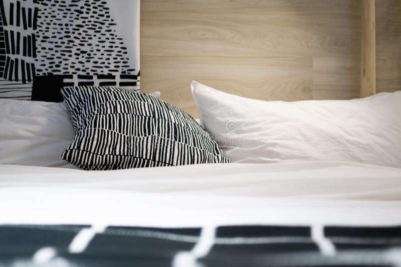 Descansos e coxim preto e branco na cama no quarto acolhedor fotografia de stock
