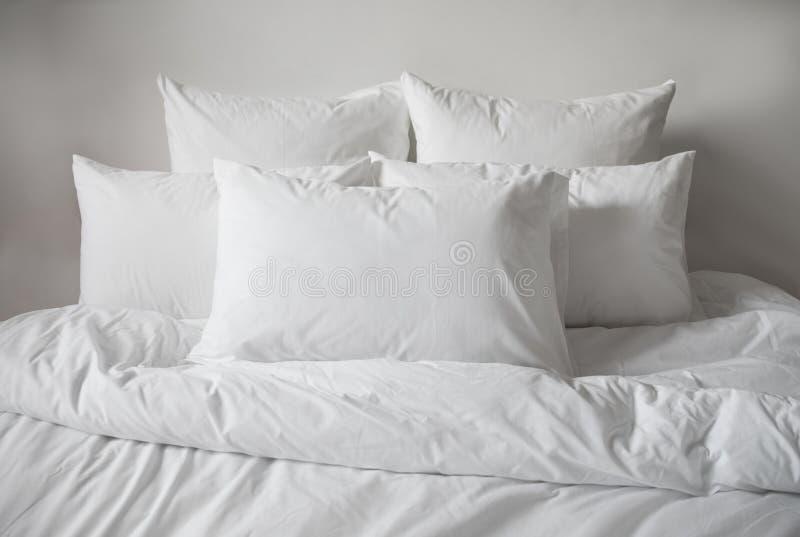 Descansos, edredão e duvetcase brancos em uma cama Vista lateral fotografia de stock royalty free