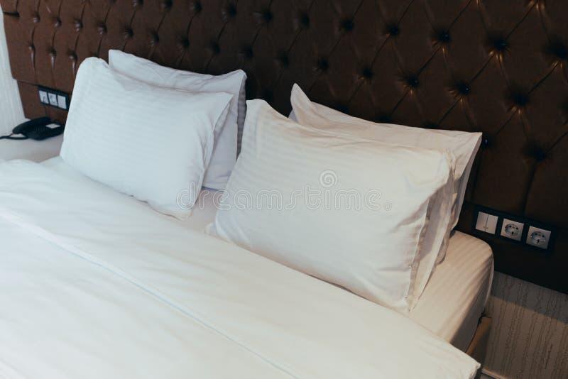 Descansos macios confort?veis na cama Folhas e descanso brancos do fundamento do close-up no fundo claro da sala da parede Concei fotografia de stock