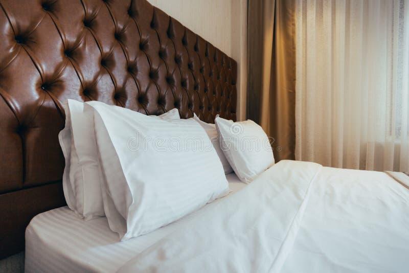 Descansos macios confort?veis na cama Folhas e descanso brancos do fundamento do close-up no fundo claro da sala da parede Concei fotos de stock
