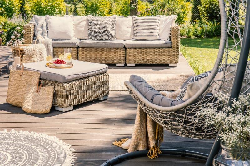 Descansos no sofá e na tabela do rattan no pátio com cadeira de suspensão du imagem de stock