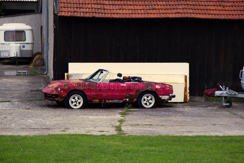 Descapotable viejo del coche de deportes lanzado en la yarda imagenes de archivo