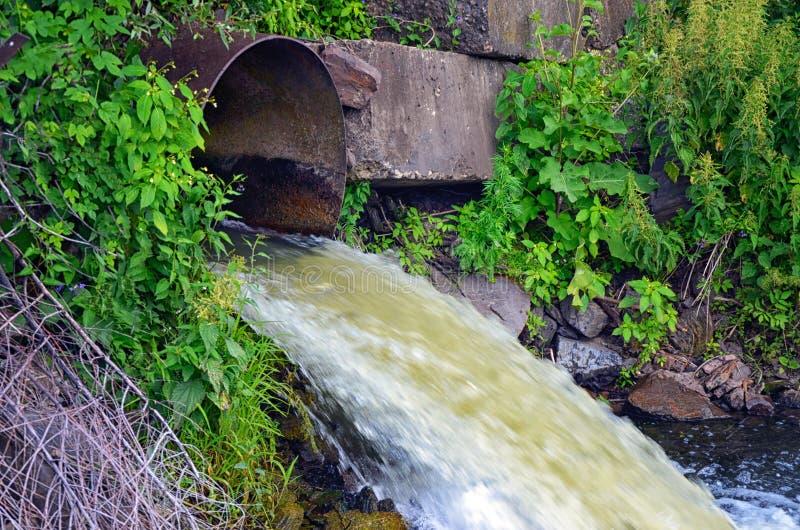 Descarga da água da tubulação no rio imagem de stock