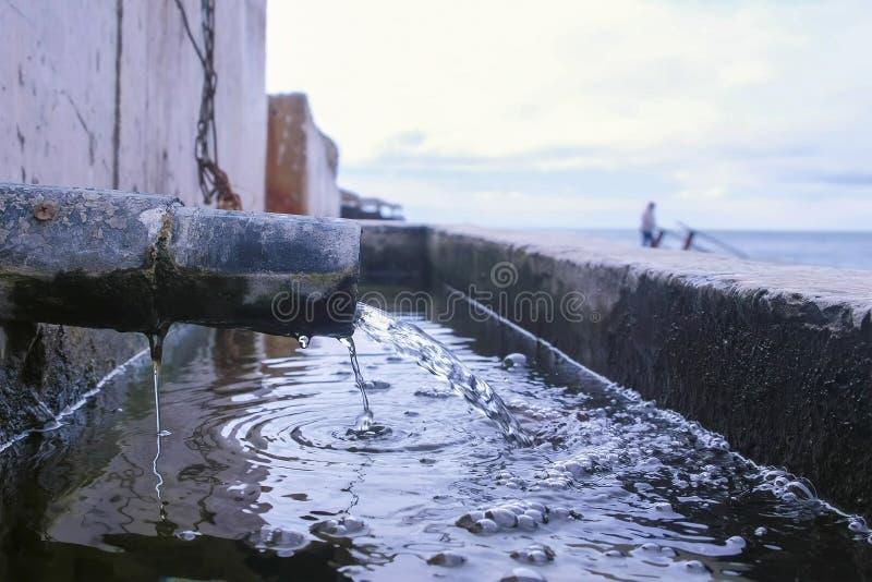 Descarga de águas residuais industriais sujas no mar na margem imagem de stock