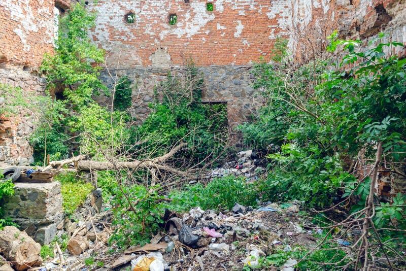 Descarga de basura en el edificio destruido viejo, protección del medio ambiente imágenes de archivo libres de regalías