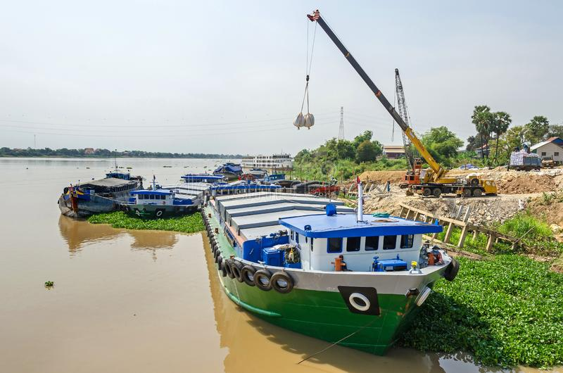 Descarga de la carga del buque de carga en el río Mekong en Camboya fotos de archivo