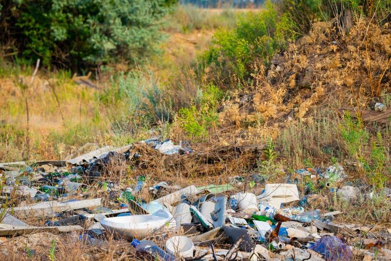 Descarga de lixo na grama perto da floresta, conceito do desastre ecológico, natureza poluir fotografia de stock royalty free