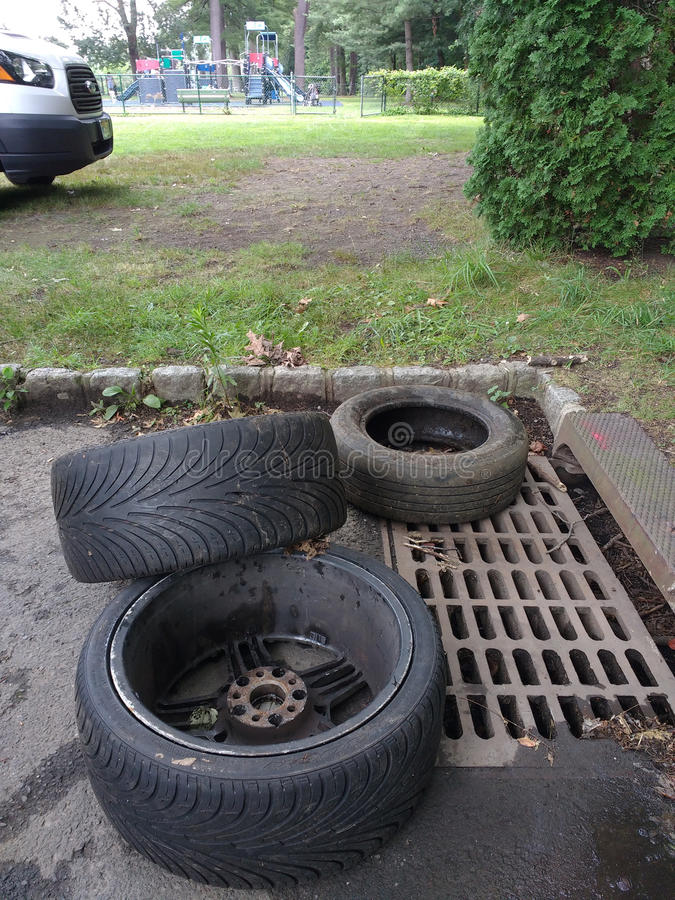 Descarga ilegal, neumáticos cerca de un dren de la tormenta imagenes de archivo