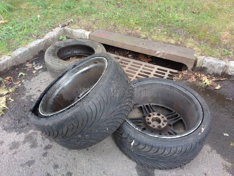 Descarga ilegal, neumáticos cerca de una alcantarilla de la tormenta fotos de archivo libres de regalías