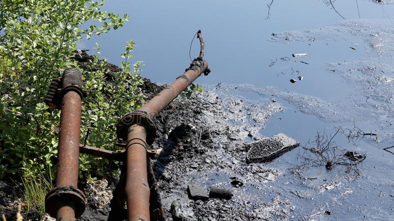 Descargue la basura tóxica, el agua de la contaminación de la laguna del aceite y el suelo imagen de archivo