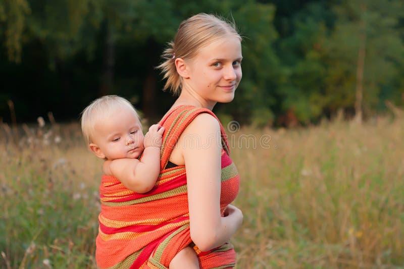 Descendant de transport de mère dans l'élingue photos libres de droits