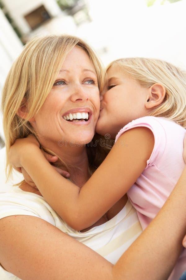 Descendant donnant le baiser de mère détendant sur le sofa image libre de droits