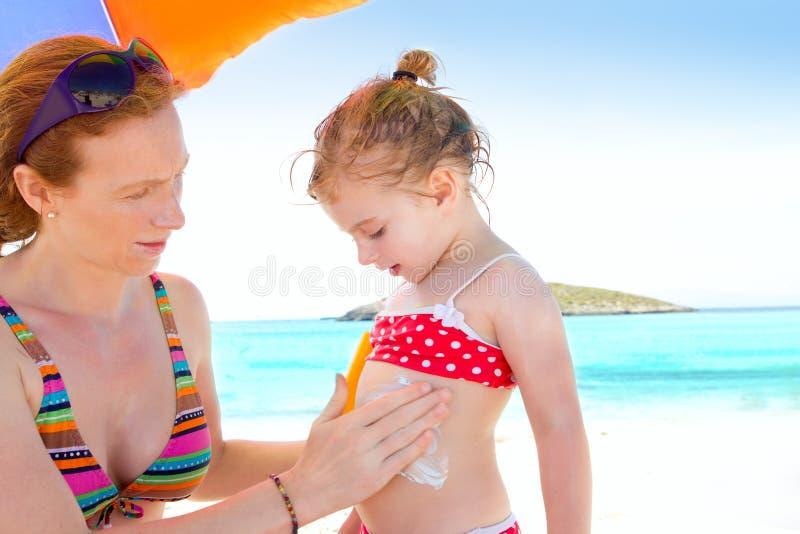 Descendant et mère en plage avec la protection solaire photographie stock