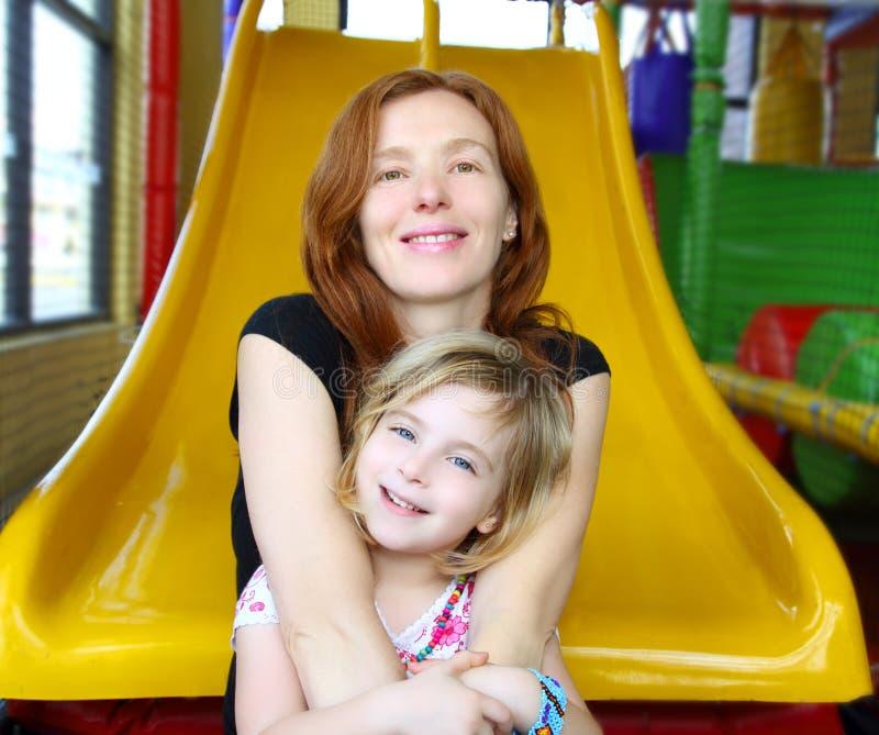 Descendant et mère ensemble dans la glissière de cour de jeu images libres de droits