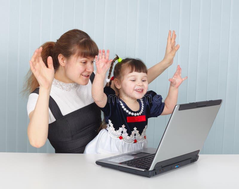 Descendant et mère jouant avec l'ordinateur portatif image stock