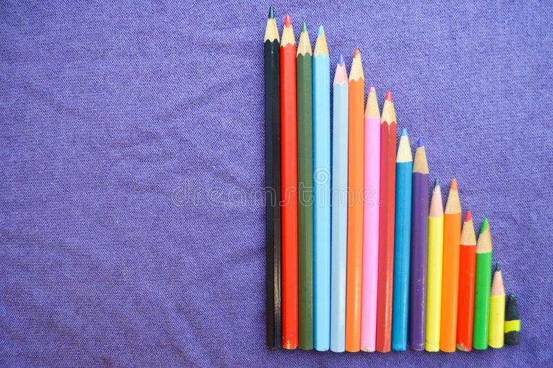 A descending chart of colorful, bright, variegated drawing pencils, a notebook royalty free stock photography
