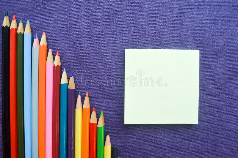 A descending chart of colorful, bright, variegated drawing pencils, a notebook stock photography