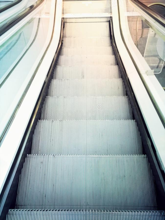 Descending escalator moving stairs in city shopping mall or business office building. Abstract concept of direction destination mo royalty free stock image
