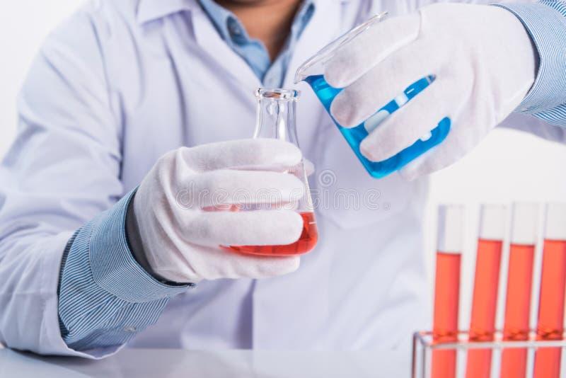 Descenso del científico cemical en el tubo de ensayo del laboratorio en tabl de trabajo imágenes de archivo libres de regalías