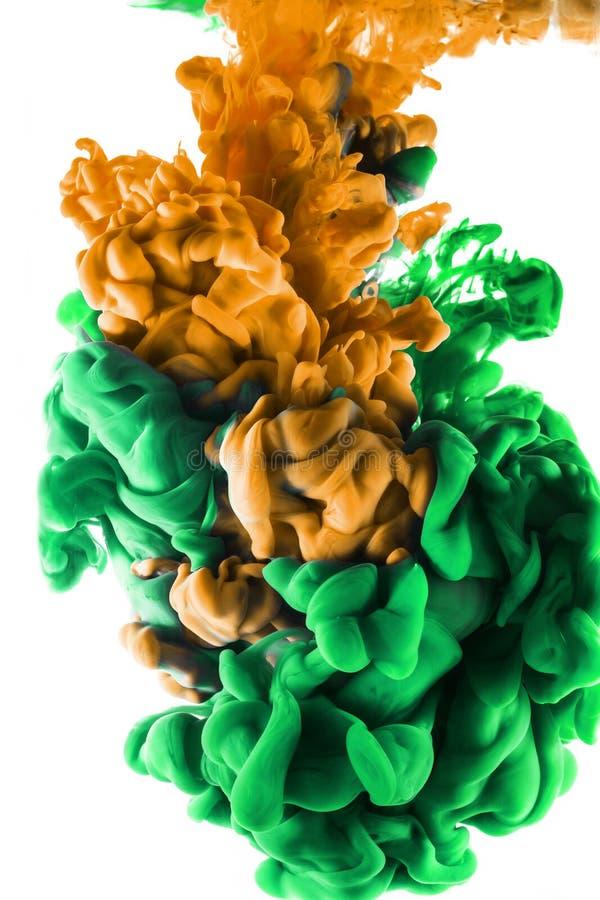 Descenso del color Tinta anaranjada y verde en el fondo blanco foto de archivo