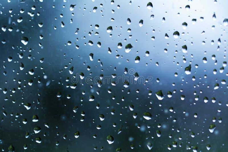 Descensos del agua de lluvia en un vidrio de la ventana imagen de archivo