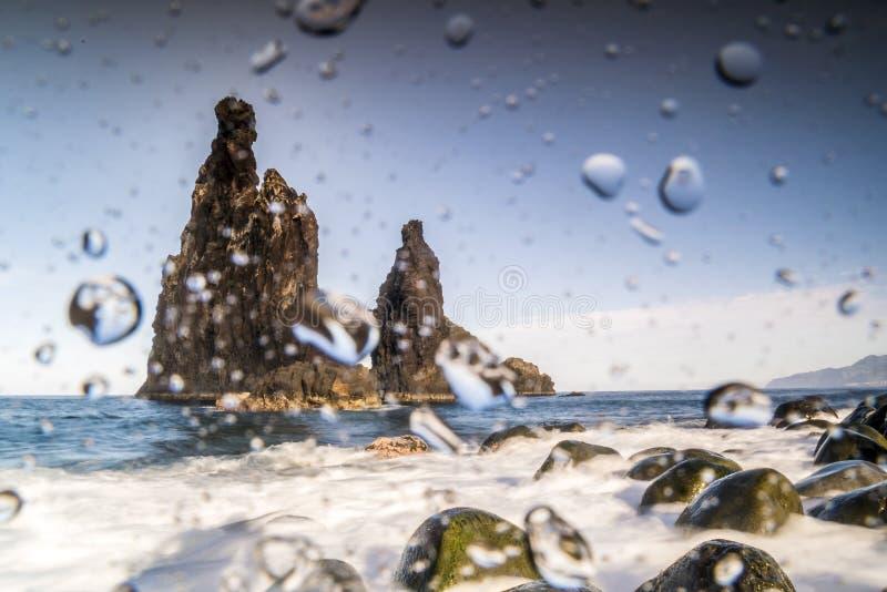 Descensos del agua en la lente que fotografía rocas en Océano Atlántico fotografía de archivo