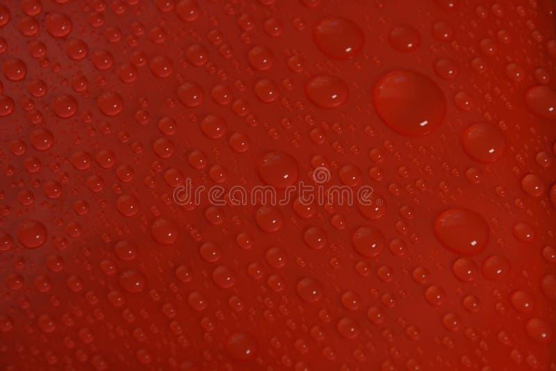 Descensos del agua en textura roja del fondo foto de archivo libre de regalías