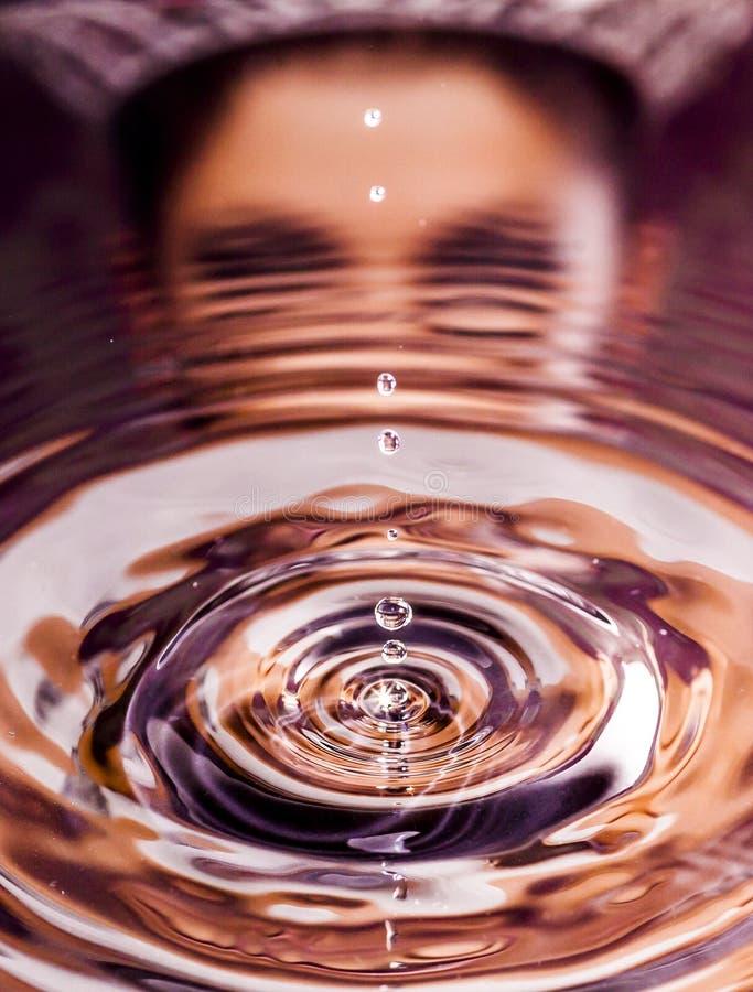Descensos puros del agua con la chispa y la mujer estupendas con la reflexión de la corona imágenes de archivo libres de regalías
