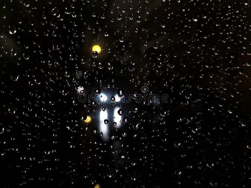 Descensos sobre el vidrio en la noche con tráfico ligero foto de archivo