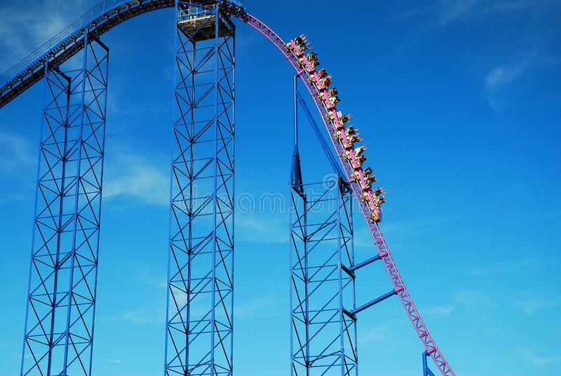 On the Descent. Riders on an extreme roller coaster raise their arms up as the are going down stock photos