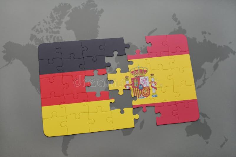 desconcierte con la bandera nacional de Alemania y de España en un fondo del mapa del mundo fotografía de archivo