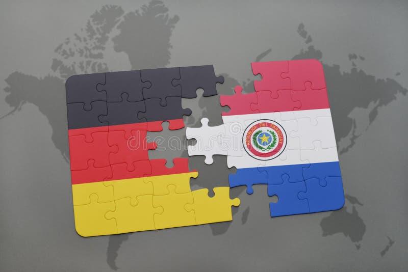 desconcierte con la bandera nacional de Alemania y de Paraguay en un fondo del mapa del mundo fotos de archivo libres de regalías