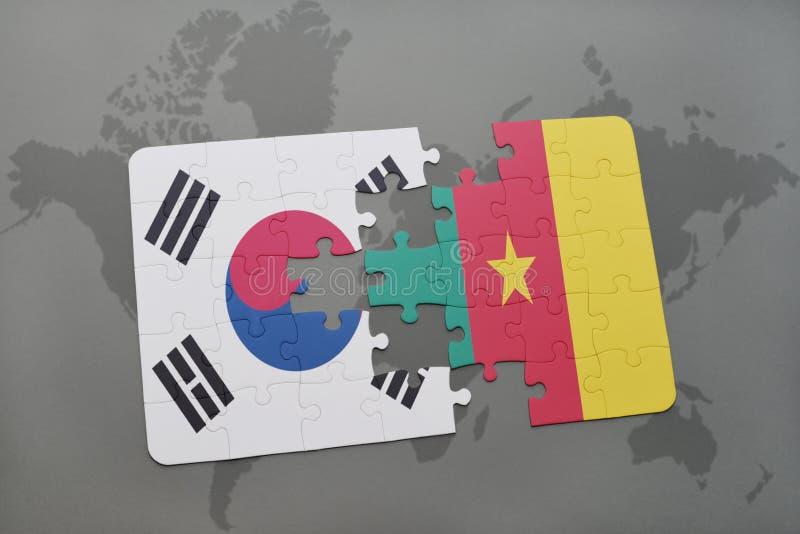 desconcierte con la bandera nacional de la Corea del Sur y del Camerún en un fondo del mapa del mundo foto de archivo