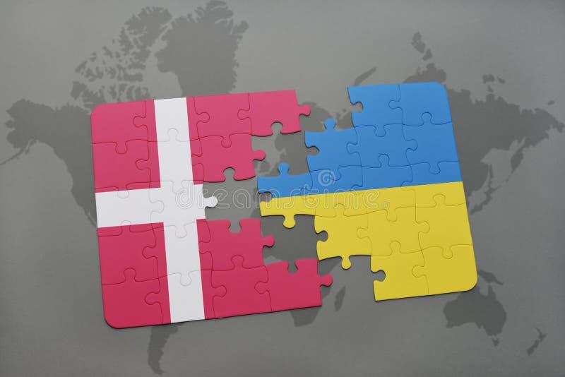 desconcierte con la bandera nacional de Dinamarca y de Ucrania en un fondo del mapa del mundo imagen de archivo libre de regalías