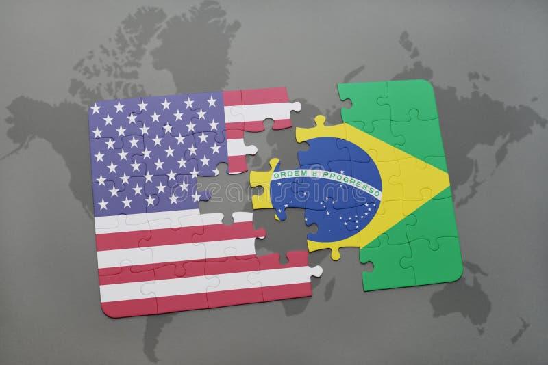 Desconcierte con la bandera nacional de los Estados Unidos de América y del Brasil en un fondo del mapa del mundo fotografía de archivo