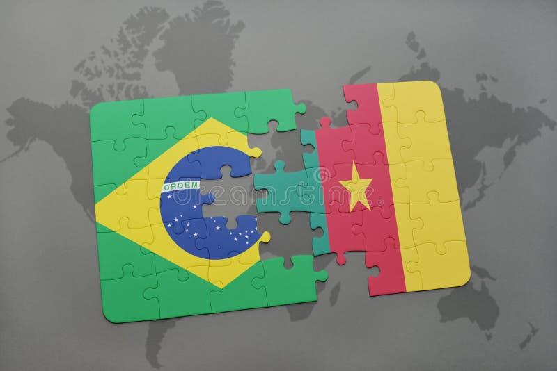 desconcierte con la bandera nacional del Brasil y del Camerún en un fondo del mapa del mundo imagenes de archivo