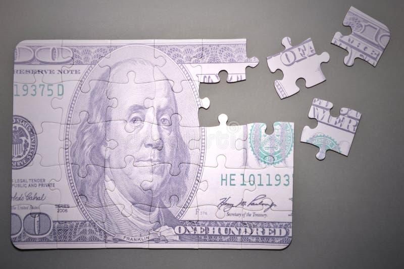Desconcierte con los cientos dólares de billete de banco en un fondo gris fotografía de archivo
