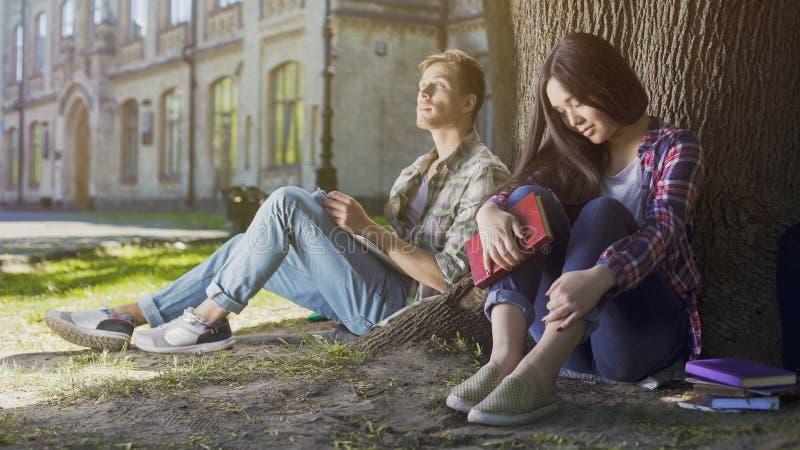 Desconhecido masculinos e fêmeas que sentam-se sob a árvore, primeira reunião, indecisiveness foto de stock royalty free
