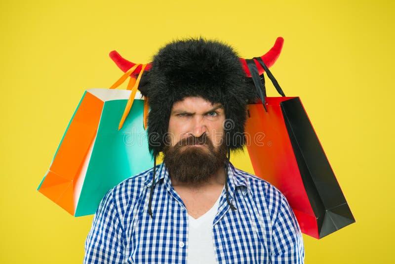 Descontentado com compra Moderno infeliz com sua compra em uns sacos de papel que penduram em chifres de touro Homem farpado brut imagens de stock
