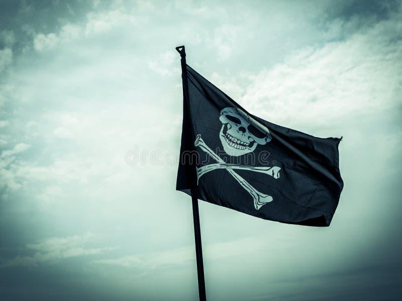 Descrição da bandeira de pirata crânio-e-ossos cruzados imagens de stock royalty free