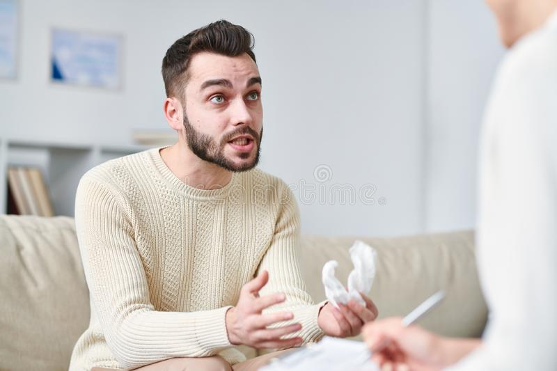 Describing problem. Stressed young men with handkerchief explaining counselor the point of his problem while sitting in front of him stock image