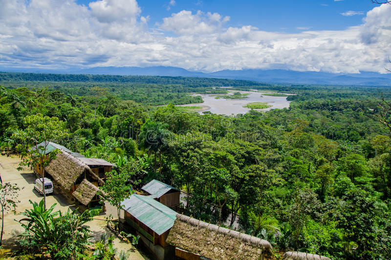 Descripción fantástica del valle de la selva del Amazonas con el río y de las cascadas en la distancia, algunas pequeñas casas si fotografía de archivo libre de regalías