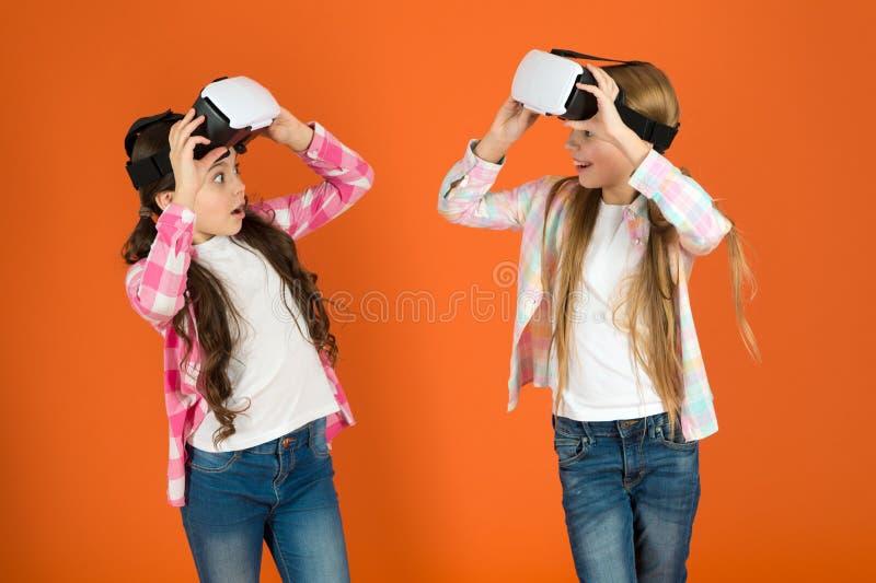Descubra a realidade virtual As meninas das crianças jogam o jogo da realidade virtual Os amigos interagem no vr Explore a realid imagens de stock