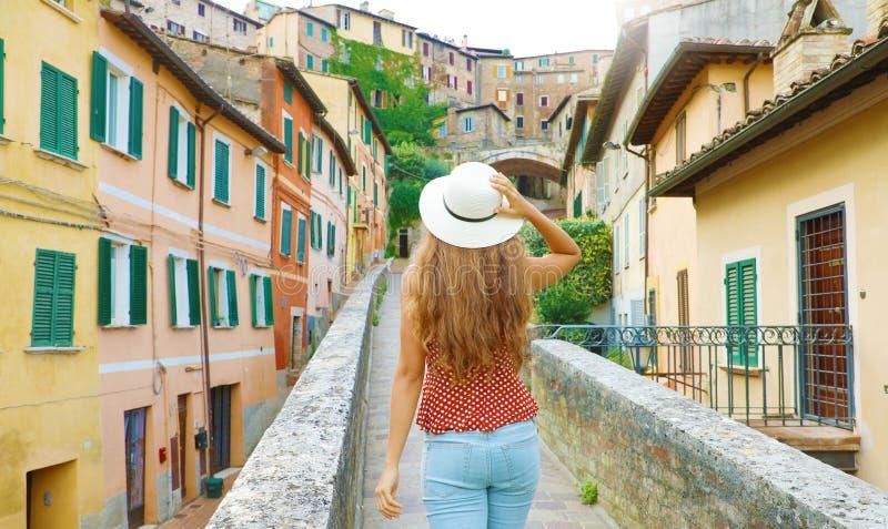Descubriendo Italia. Vista posterior de una joven atractiva mujer caminando por la antigua ciudad italiana imagen de archivo libre de regalías
